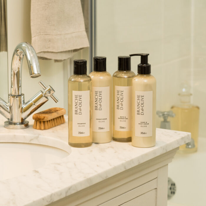 Four Branche d'Olive bottles of Shampoo, Conditioner, Bath & Shower Gel and Hand & Body Cream in Olive fragrance next to a marble bathroom sink