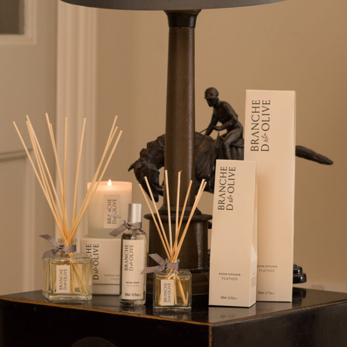 Branche d'Olive Feather large and small Room Diffusers, Room Spray and Scented Candle on a dark wooden table