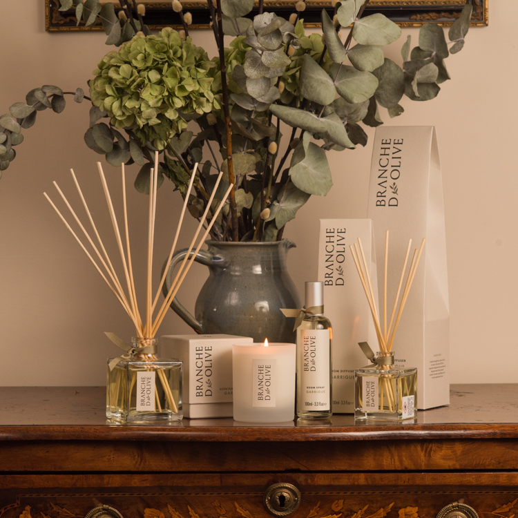Branche d'Olive Garrigue large and small Room Diffusers, Candle and Room Spray on a wooden table in front of some green flowers