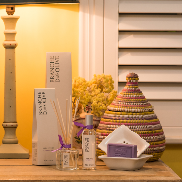 Branche d'Olive Lavender Room Diffuser, Room Spray, Soap and Soap Dish on a wooden table in front of some yellow flowers