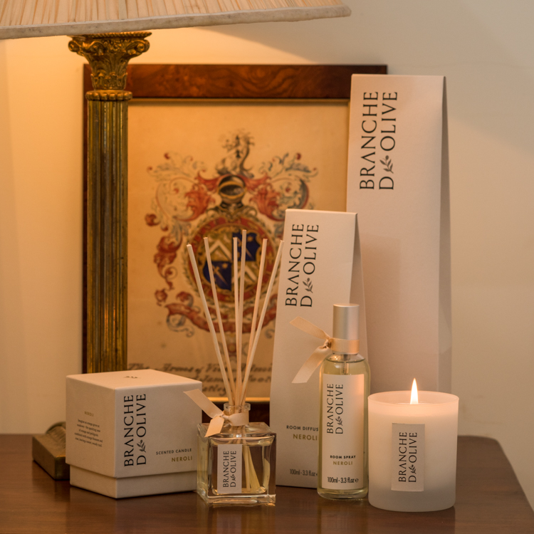 Branche d'Olive Neroli scented Room Diffuser, Room Spray and Candle on a wooden table in front of a classic picture