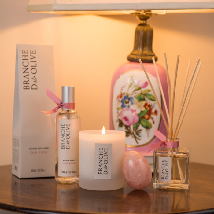 Branche d'Olive Old Rose Room Diffuser, Candle and Room Spray on a wooden table in front of a pink lamp