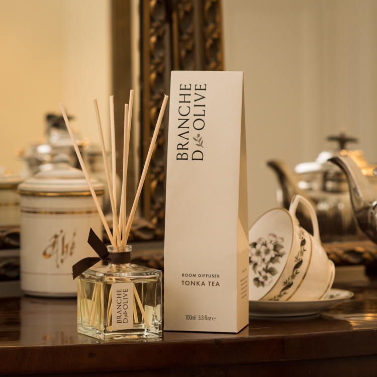 Branche d'Olive Room Diffuser in Tonka Tea fragrance on a wooden table with tea cups and teapots