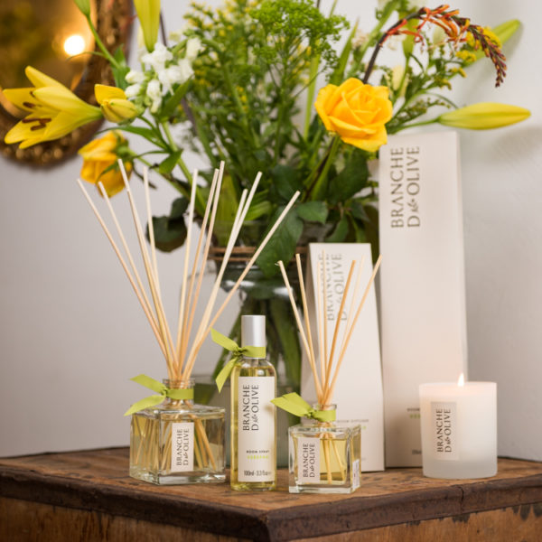 Branche d'Olive Verbena large and small Room Diffusers, Candle and Room Spray on a wooden table in front of some yellow flowers