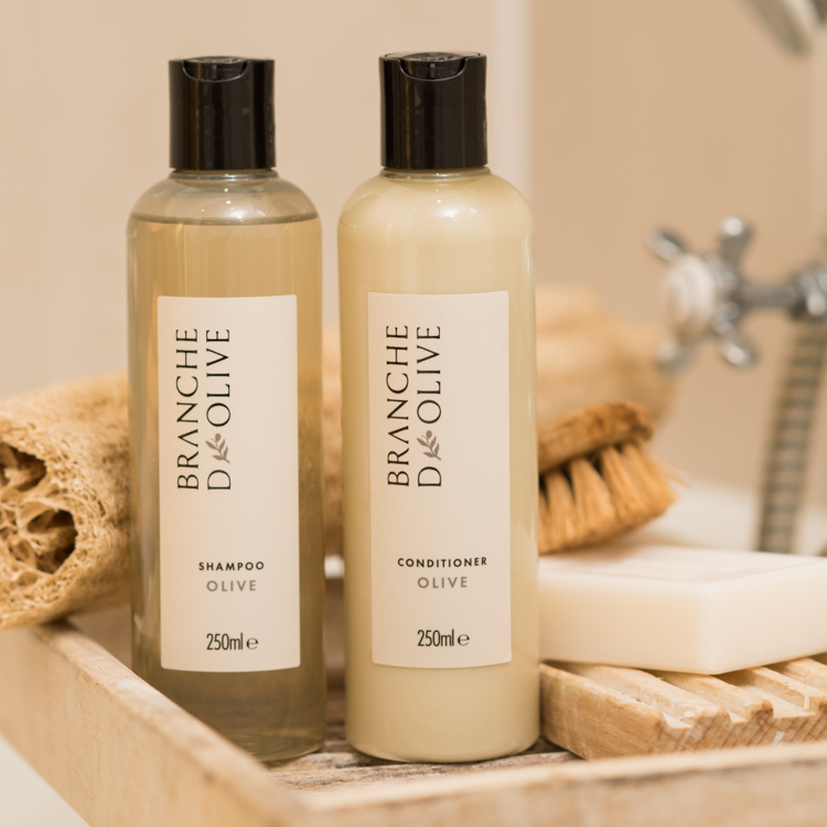 Bottles of Branche d'Olive Olive fragranced Shampoo and Conditioner a wooden bath caddy in a bathroom